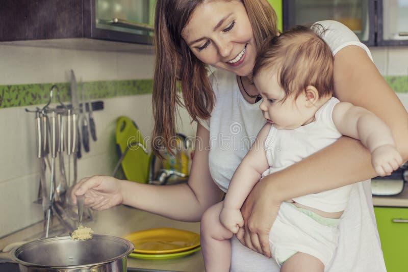 Modern av en kvinna med en behandla som ett barn lagar mat maten i en kruka på stoen arkivfoton