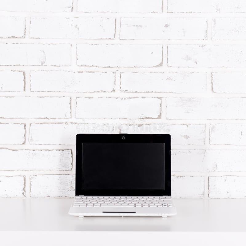 Modern bärbar dator med den tomma skärmen på tabellen över den vita tegelstenwaen royaltyfria bilder