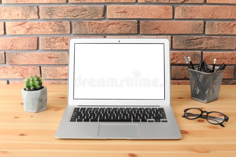 Modern bärbar dator på tabellen mot tegelstenväggen Åtlöje upp royaltyfri bild