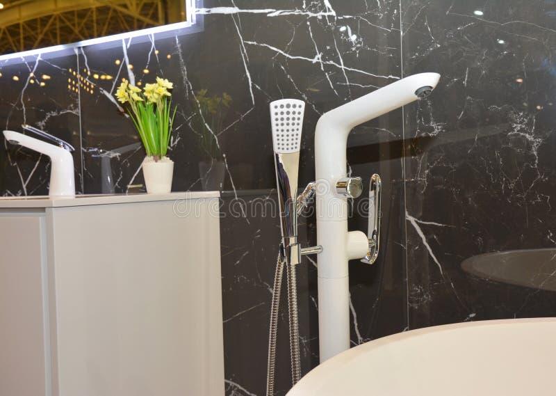 Modern baddusch med marmorväggar, badvattenkranen och badvasken arkivbilder