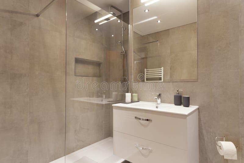 Modern badrum med bruna plattor royaltyfria bilder