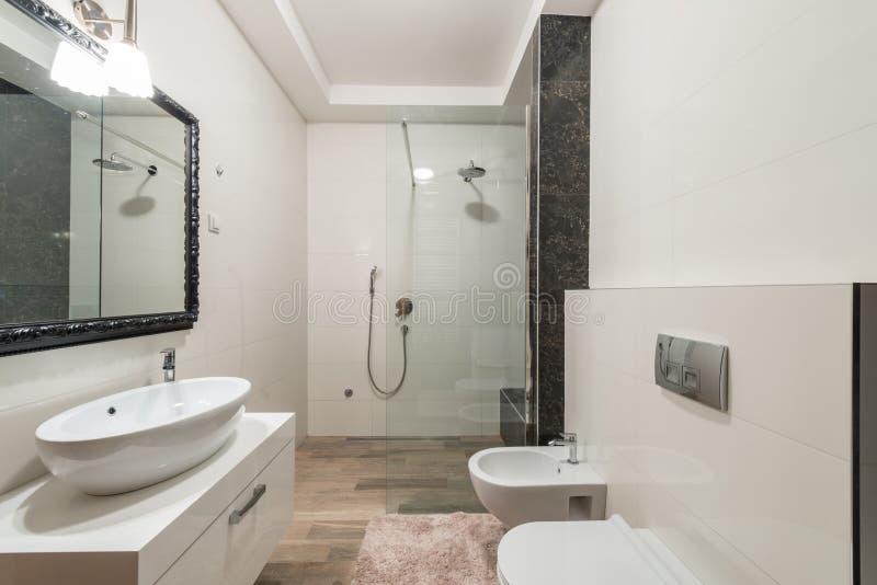 Modern badruminre med duschkabinen i lyxig villa royaltyfria bilder