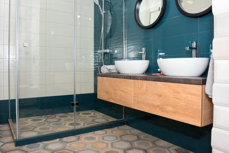 Modern badruminre med en trähylla, två vaskar som står på den, och runda speglar Genomskinlig glass duschkabin arkivfoto
