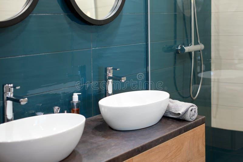 Modern badruminre med en tr?hylla, tv? vaskar som st?r p? den, och runda speglar Genomskinlig glass duschkabin royaltyfri foto