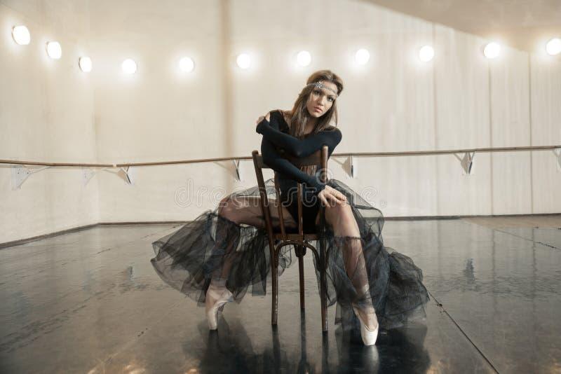 Modern balettdansör på en trästol på en upprepning arkivfoton