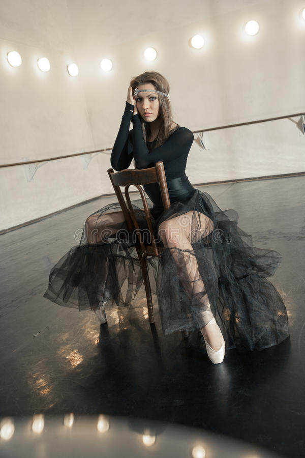 Modern balettdansör på en trästol på en upprepning royaltyfri fotografi