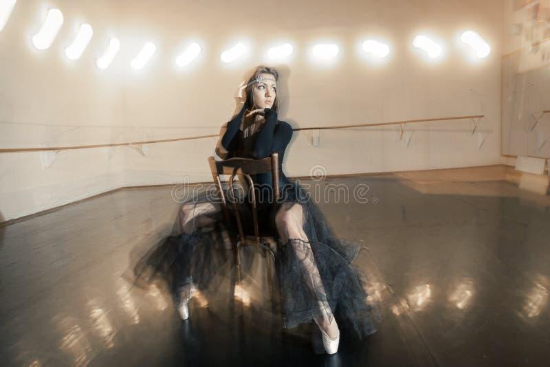 Modern balettdansör på en trästol på en upprepning royaltyfri bild