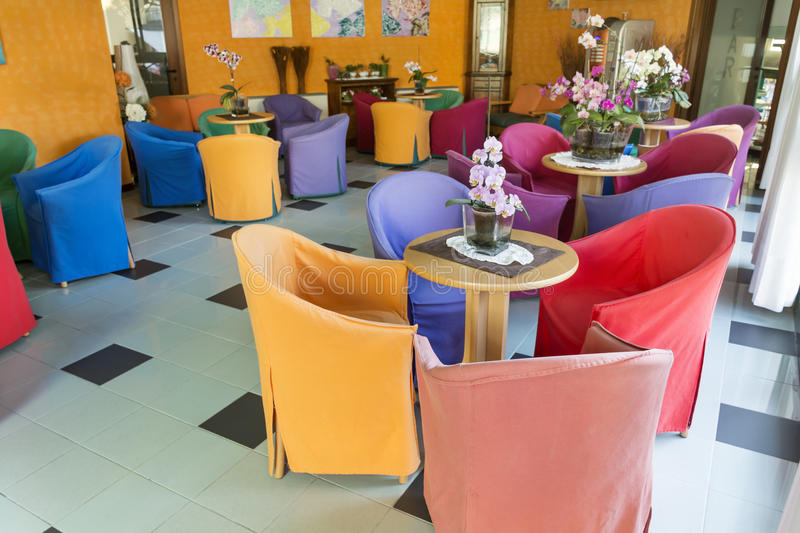 Modern bar interior with colorful chairs. Italian cozy bar with colorful tables , chairs and orchid flowers royalty free stock image