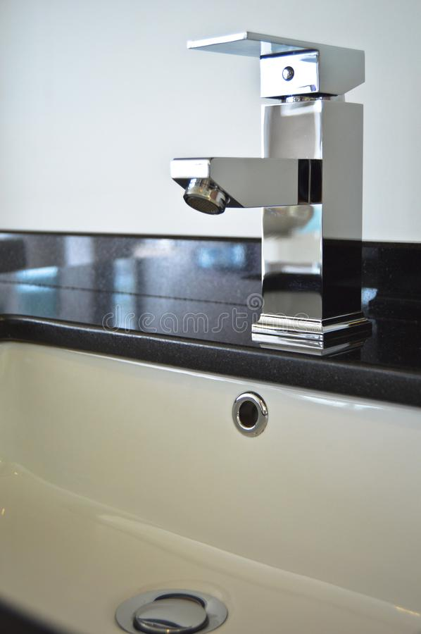 Modern bathroom taps. Cleaning, drought. A modern basin mixer tap in a contemporary bathroom royalty free stock photos