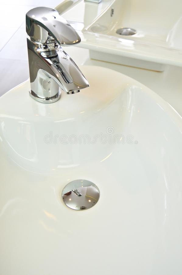 Modern bathroom taps. Cleaning, drought. A modern basin mixer tap in a contemporary bathroom stock image