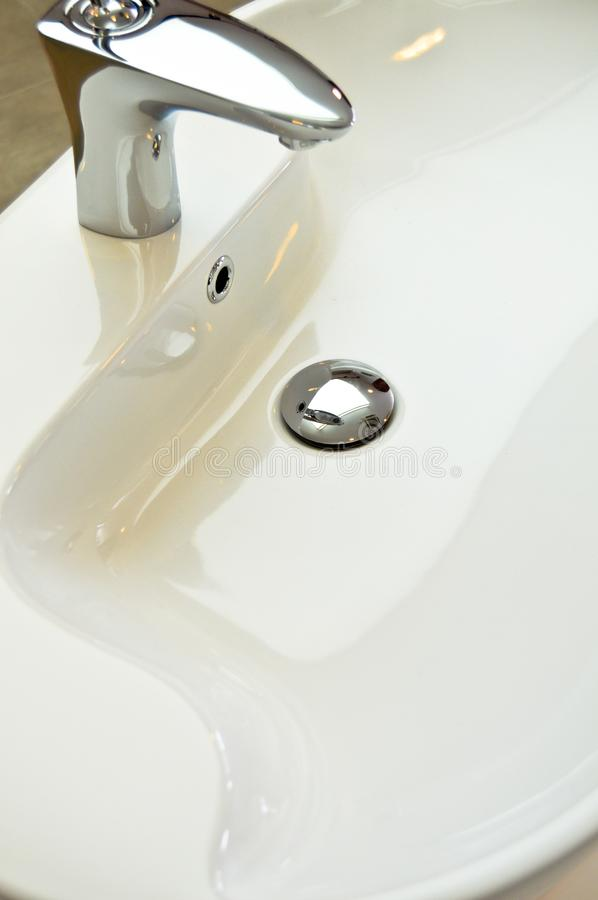 Modern bathroom taps. Cleaning, drought. A modern basin mixer tap in a contemporary bathroom stock photo