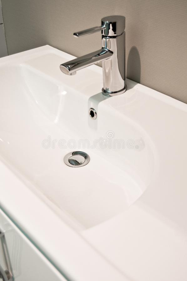 Modern bathroom taps and sing. Cleaning, drought. A modern basin mixer tap in a contemporary bathroom royalty free stock photography