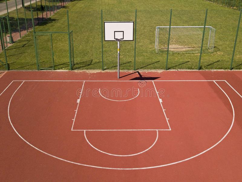 Modern basketball court in the courtyard of primary school. Multifunctional children`s playground with artificial surfaced fenced. With mesh fence.Place of stock photo