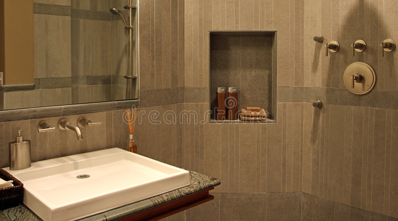 Modern Bathroom. Upscale modern bathroom with a flat sink and stone walls almost creates a spa like atmosphere royalty free stock image