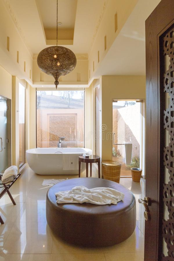 Modern bathroom area with bath tub and sofa inside in the morning at Abu Dhabi, UAE.  royalty free stock image