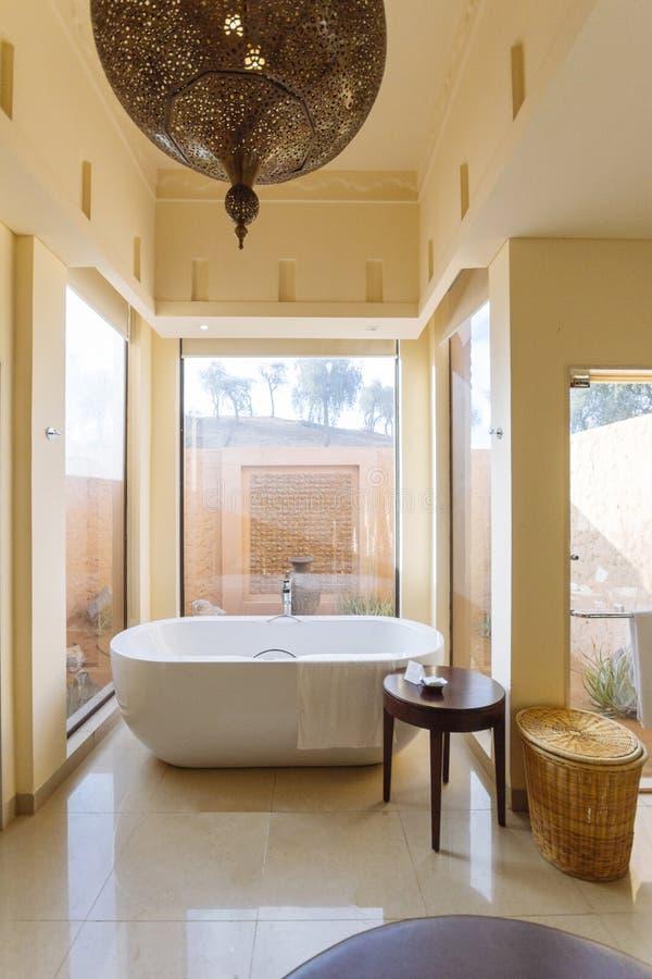 Modern bathroom area with bath tub and sofa inside in the morning at Abu Dhabi, UAE.  stock image