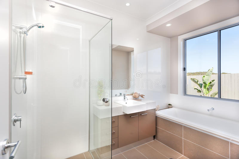 Modern bathroom with a faucet, water tub and a dark brown floor. Bathroom of a luxurious house with bathing area from the left side surround by glasses and a stock photography