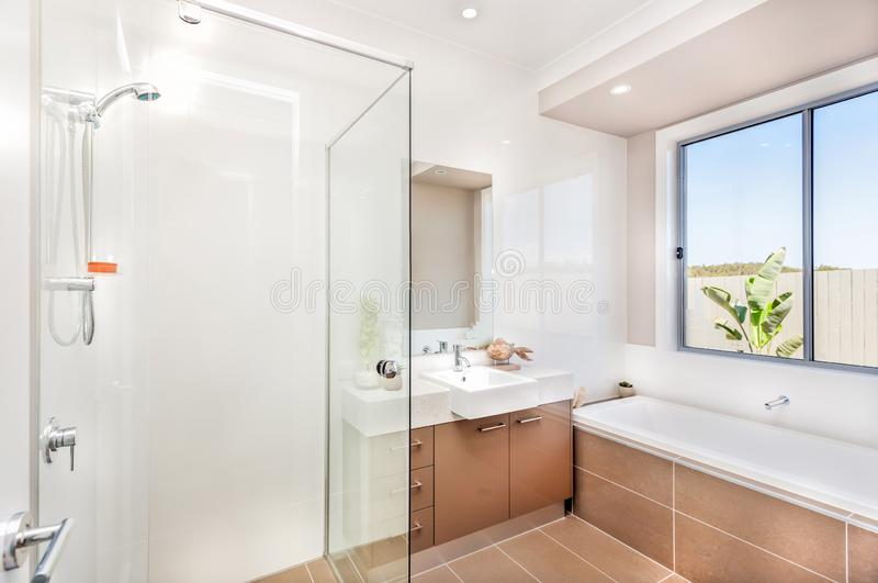 Modern bathroom with a faucet, water tub and a dark brown floor tiles. A bathroom of a luxurious house with bathing area from the left side surround by glasses royalty free stock photography