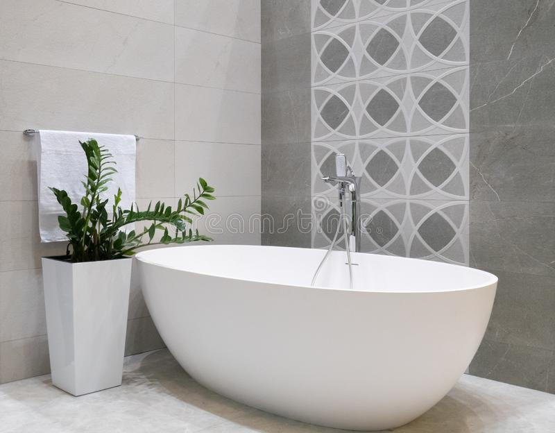 Modern bathroom interior design with white stone bathtub, grey tiles wall, ceramic flowerpot with green plant and hanger with stock photos