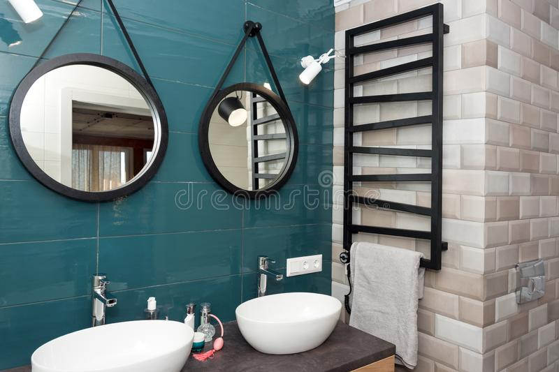 Modern bathroom interior with a wooden shelf, two sinks standing on it and round mirrors. Transparent glass shower cabin. Minimalist scandinavian bathroom in stock photography