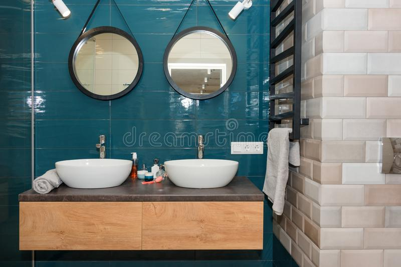 Modern bathroom interior with a wooden shelf, two sinks standing on it and round mirrors. Transparent glass shower cabin. Minimalist scandinavian bathroom in stock photos