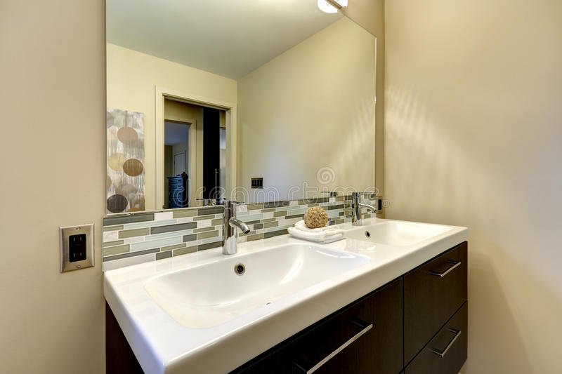 Modern bathroom large double white sink with mirror. Modern bathroom large double white sink counter top with mirror and brown cabinet stock images