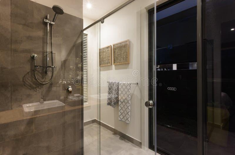 Modern bathroom shower area with glass doors stock image