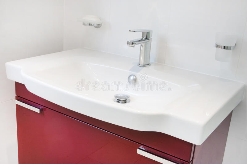 Modern bathroom sink unit. Contemporary modern bathroom red cabinet and built in sink and taps royalty free stock photos