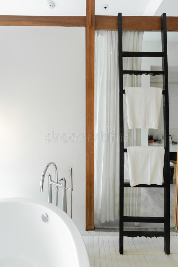 Modern Bathroom in modern style with empty white painted wall and black wooden ladder towel rack in tropical resort / copyspace / stock photo