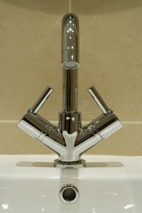 Modern bathroom tap. A modern basin mixer tap in a contemporary bathroom royalty free stock photo