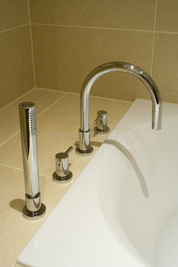 Modern bathroom taps. Contemporary taps in a modern designer bathroom royalty free stock photo