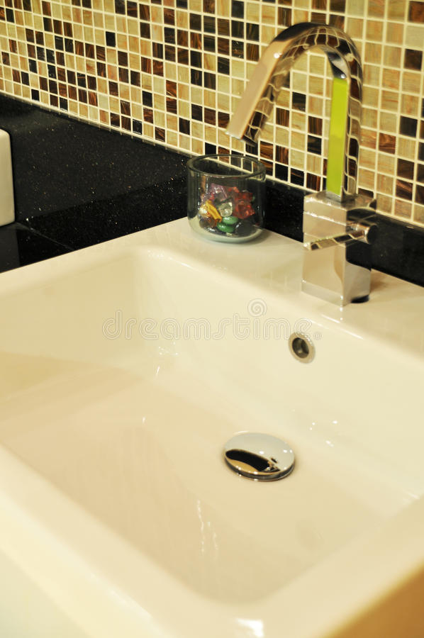 Modern bathroom taps. A modern basin mixer tap in a contemporary bathroom royalty free stock photography