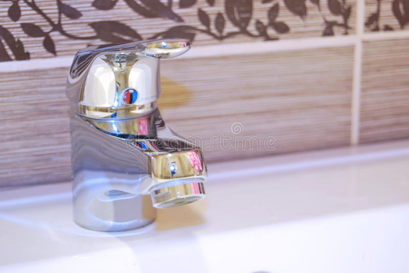 Modern bathroom taps. A modern basin mixer tap in a contemporary bathroom royalty free stock photo