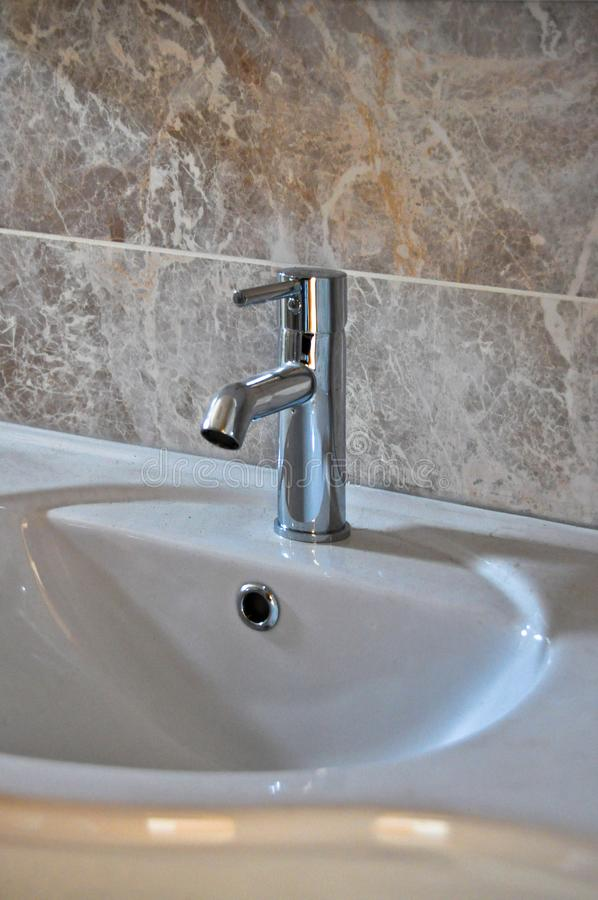 Modern bathroom taps. Cleaning, drought. A modern basin mixer tap in a contemporary bathroom royalty free stock image