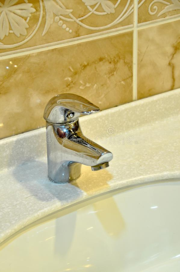 Modern bathroom taps. Cleaning, drought. A modern basin mixer tap in a contemporary bathroom royalty free stock images