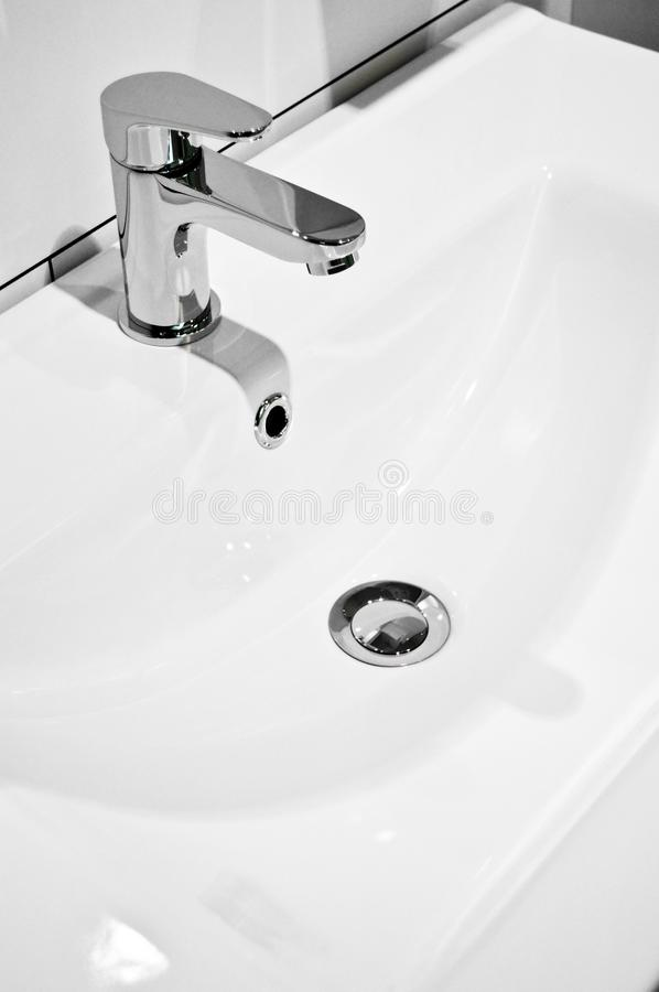Modern bathroom taps and sing. Cleaning, drought. A modern basin mixer tap in a contemporary bathroom royalty free stock photos