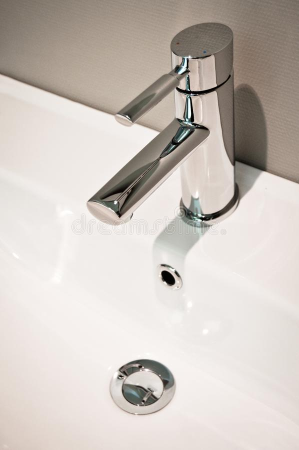 Modern bathroom taps and sing. Cleaning, drought. A modern basin mixer tap in a contemporary bathroom stock photo