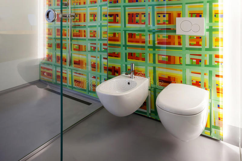 Modern bathroom, toilet and bidet. And colored tiles on the wall royalty free stock image