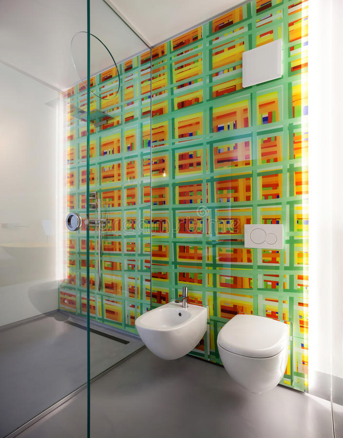 Modern bathroom, toilet and bidet. And colored tiles on the wall stock images