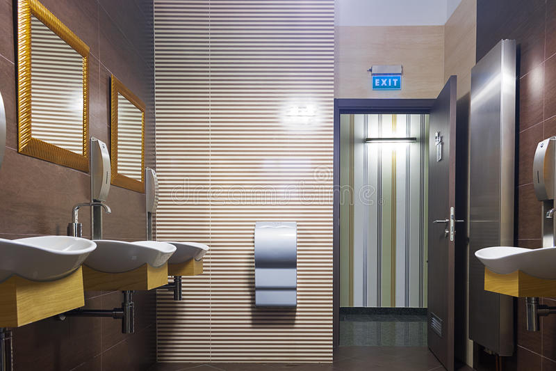 Modern bathroom. Wide angle of a modern bathroom with sinks, mirrors, hand dryer and an open door with Exit sign above that enters a lobby stock image
