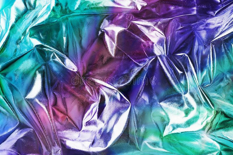 Modern beautiful holographic background of crumpled foil. Trendy 80`s style. royalty free stock image