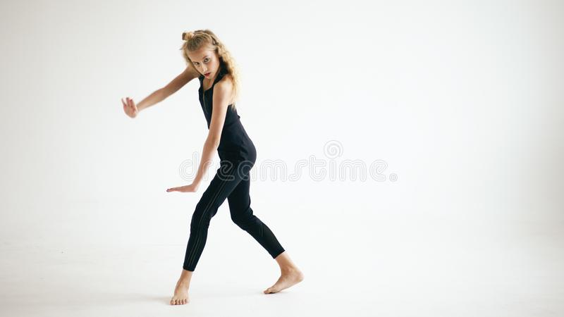 Modern beautiful teenage girl dancer dancing contemporary on white background indoors. Modern beautiful teenage girl dancer dancing contemporary on white stock image
