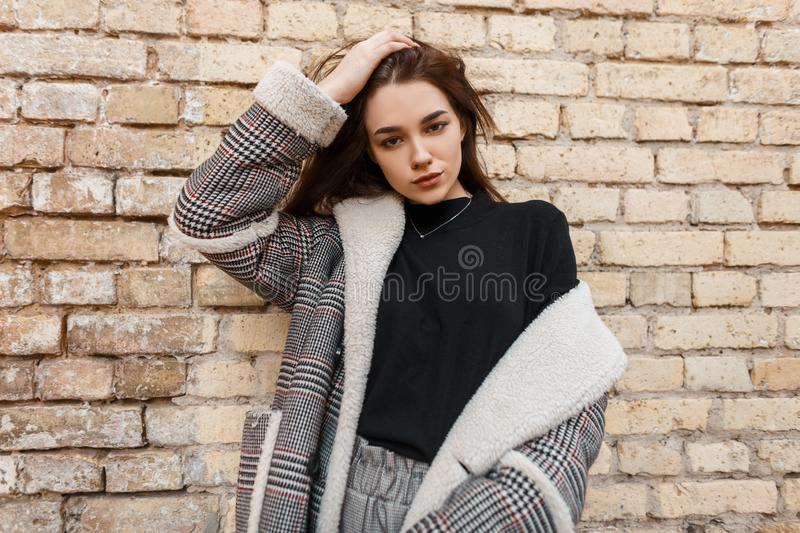 Modern beautiful young brunette woman in a black T-shirt in a vintage checkered jacket in gray fashionable trousers posing. Near an old brick building outdoors royalty free stock image