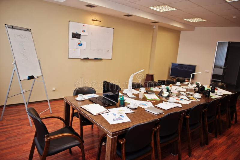 Modern bedrijfsbureaubinnenland die lijsten en stoelen, laptop, camera en bureaulevering zonder werknemers bevatten royalty-vrije stock foto's