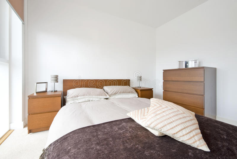 Modern bedroom detail with modern furniture. Detail of a double bedroom with king size bed, chest of drawers and bedside tables royalty free stock photography