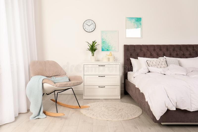 Modern bedroom interior with comfortable chair. Stylish design royalty free stock image