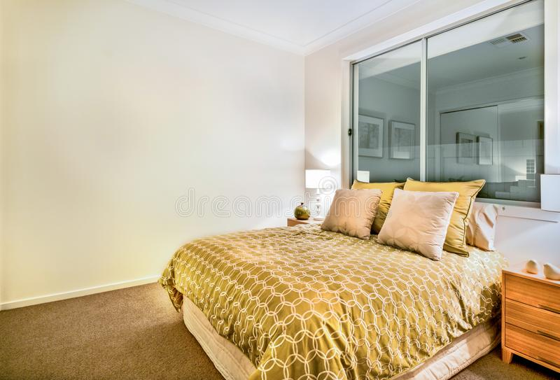 Modern bedroom interior in a luxurious apartment with king size bed stock images