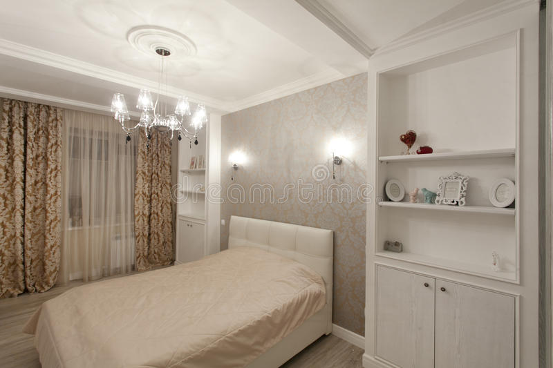 Modern Bedroom interior. In warm tones with chandelier royalty free stock image