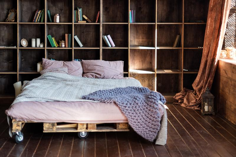 Modern bedroom in a loft. Urban apartment with pallet bed, scandinavian eco design. stock photo