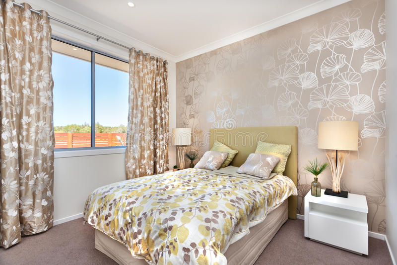 Modern bedroom with a master bed and light brown color curtain d. Luxury bed is little bit tall from the carpet floor and it has a light color bed sheet with stock photography